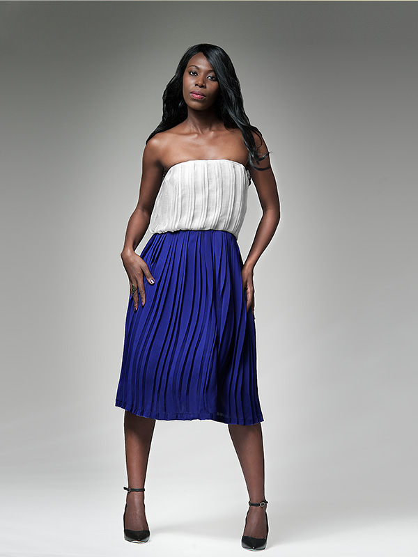 black female model in blue skirt and white top